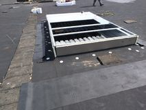 Roofing repairs in progress on Commercial EPDM roof; AC curb wrapping; Flat stock photo