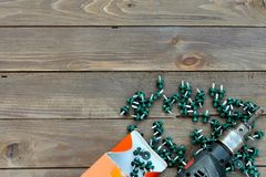 Roofing screws and a drill on a wooden table. The view from the top. Place for advertising and labels.Roofer, roofing work.  Royalty Free Stock Photography
