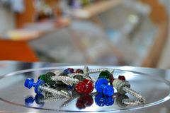 Roofing screws, painted in different colors, hanging in the balance in the store, with copyspace stock photography