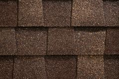 Roofing Shingles. A close-up of brown toned architectural style asphalt roofing shingles Royalty Free Stock Images