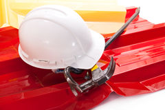 Roofing. White working helmet, red and yellow plastic roof with acrylic coating, hammer and crowbar Royalty Free Stock Image