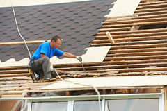 Roofing work with flex roof. Worker on roof at works with flex tile material demounting roofing stock images