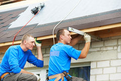 Roofing work with flex roof. Worker on roof at works with flex tile material mounting roofing royalty free stock photo