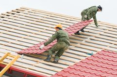 Roofing work with metal tile. Two workers on roof at works with metal tile and roofing iron Stock Images