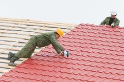 Roofing work with metal tile. Two workers on roof at works screwdriving metal tile and roofing iron Stock Photography