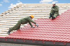 Roofing work with metal tile. Two workers on roof at works with metal tile and roofing iron Royalty Free Stock Images
