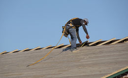 A roofing worker with tape measure. Florida USA - October 2016 - Roofer wearing a safety harness measuring wooden slats using a tape measure Royalty Free Stock Photography