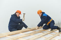 Roofing workers hammer roof boarding Royalty Free Stock Images