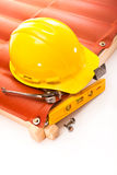 Roofing. Yellow hard hat, pliers, screws, scrap, and the level of the roof with a wooden frame Stock Images