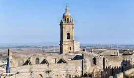 Roofless church. Bell along with ruins of a roofless church, the background is a rural landscape with windmills, is located in the town of Medina Sidonia in Royalty Free Stock Images