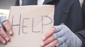 Roofless person asking for help in center of city with help sign
