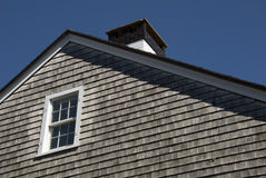Roofline. Of a typical New England house showing traditional wooden shingles Royalty Free Stock Photo