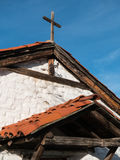Rooflines and rustic cross on historic church Stock Images