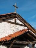 Rooflines y cruz rústica en iglesia histórica Imagenes de archivo
