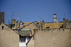 The roofs with attics, red shingles and antennas on blue sky background. royalty free stock image