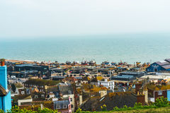 Roofs of buildings in a seaside village, in the background fishi Stock Images