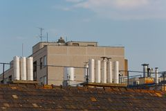 Roofs and chimneys. Chimneys on roofs in late afternoon light Royalty Free Stock Photos