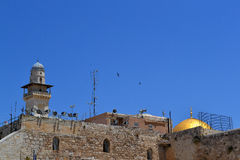 Roofs of churches and the minarets of Jerusalem in the old city on the background of blue sky with two soaring birds Royalty Free Stock Image