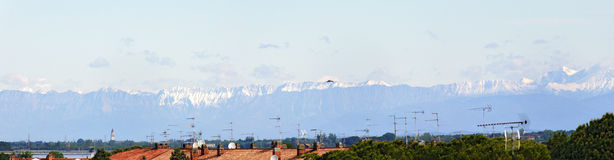 Roofs of Grado with snow-covered alps royalty free stock image
