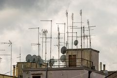 Roofs of houses full of TV antennas, satellite dishes stock photo