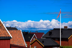 The roofs of the houses in Norway. The roofs of the brown houses in Norway, with a flag royalty free stock photo