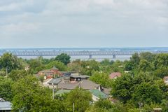 Roofs of houses, trees and a big iron bridge over the river in the distance. stock photos