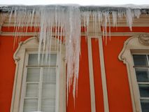 Roofs of houses and windows in huge hanging icicles. royalty free stock photography