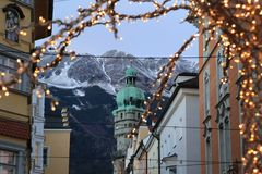 Roofs of Innsbruck with mountains and Christmas lights on a foreground at evening Royalty Free Stock Photography