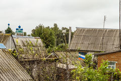Roofs of the old beggar patriotic home ownership of the old Russian village. Russian flag in a ramshackle slum Royalty Free Stock Image