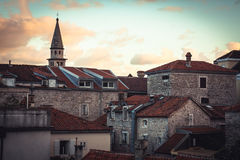 Roofs of Old European city skyline with orange tile and tower in front of dramatic sunset sky with antique architecture in old Eur Stock Images