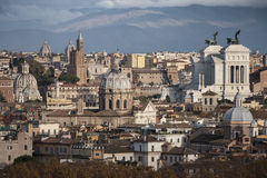 The roofs of Rome, Italy. Mountains of Lazio. An aerial view of the roofs of the ancient city of Rome in Italy. Some churches with domes, in the right altar of Stock Images