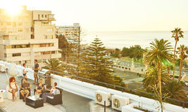 Rooftop barbaque at sunset with group of attractive young adults Royalty Free Stock Photos