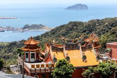 Rooftop of a Chinese Temple in Jiufen, Taiwan. The colorful and intricate rooftop of a Chinese temple on the hillside in Jiufen, New Taipei City, overlooks the Stock Photo