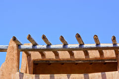 Rooftop detail of Santa Fe adobe building and wooden beams. Architectural detail of rooftop of a downtown Santa Fe adobe building typical of the area in the Royalty Free Stock Photo