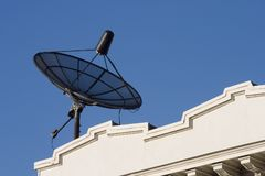 Rooftop Dish. A rooftop dish pulls in information from a satellite royalty free stock photo