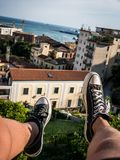 Rooftop feet dangling on italy coastline. Image showing Feet with Shoes dangling from a Rooftop with the Italy Skyline and Coast in the Background. The Feet are stock photography