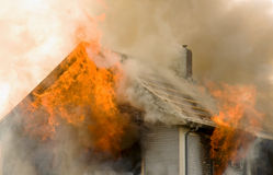 Rooftop house fire. Flames shoot out of an upper story and engulf the roof of a house on fire Royalty Free Stock Image