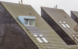 Rooftop of a modern dutch triangle shaped house, new designed architecture, dormer windows with roof tiling, homes in a small royalty free stock images