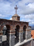 Rooftop monastery greece. Top of the monastery at lesbos seeing the cross at the top with bells stock image