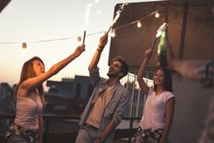 Rooftop party fireworks. Group of young friends having fun at a rooftop party, singing, dancing and waving with sparklers. Focus on the couple on the right royalty free stock photos
