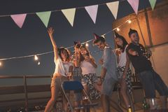 Rooftop party. Group of young friends having a birthday party at a building rooftop, singing a song and blowing a candle Royalty Free Stock Photo