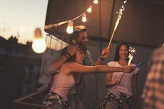 Rooftop party. Group of young friends having fun at a rooftop party, singing, dancing and waving with sparklers Stock Photography