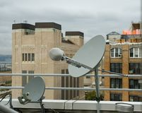 Rooftop Satellite Dishes. Two rooftop satellite dishes, poised to receive signals. New York City royalty free stock photography