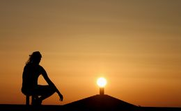 Rooftop silhouettes at sunset. A silhouetted view of a person looking into a bright sunset Royalty Free Stock Photo