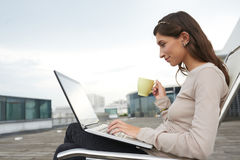 On a rooftop. Smiling pretty woman sitting on the rooftop with cup of coffee and working on laptop Stock Images