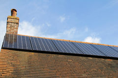 Rooftop solar power. Domestic solar panels catching the sun's rays to power the home Stock Photography