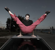 Rooftop split. Man performing a split on the roof of a car Royalty Free Stock Image