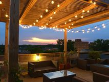 Rooftop sunset party deck. Lights and sunset light up the roof top deck in Chicago Royalty Free Stock Images