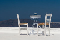 Rooftop Terrace With View. A table and two chairs decorate the roof of a typical greek house on the island of Santorini. The hills in background are another royalty free stock images