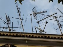 Antennas on the top of a building. Rooftop Tv antennas against blue sky stock images